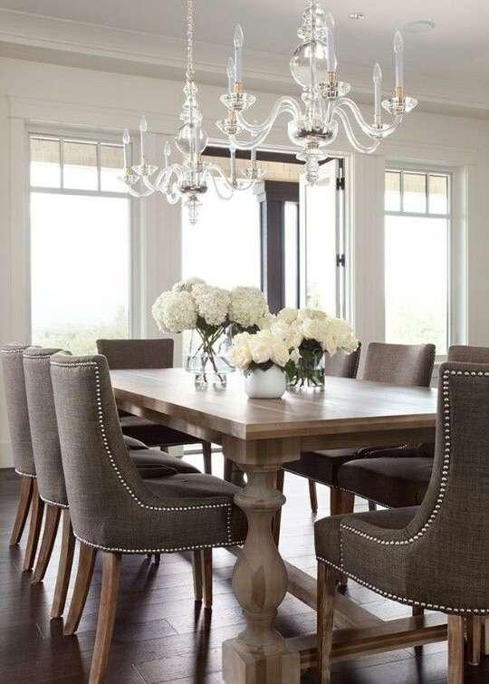 Poltroncine imbottite e fiori bianchi per questa sala da pranzo.
